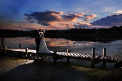 18-married-couple-kissing-on-dock-at-sunset